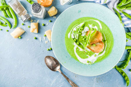 Healthy homemade green pea vegetable cream soup in a bowl on light blue slate, stone or concrete background. Copy space.