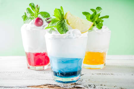 Summer cold drinks. Colorful Italian cream soda cocktails over white wooden background copy space