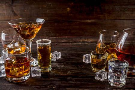 Assortimento di varie bevande alcoliche dure e forti in diversi bicchieri: vodka, cognac, tequila, brandy e whisky, grappa, liquore, vermouth, tintura, rum, ecc. Spazio di copia su fondo in legno