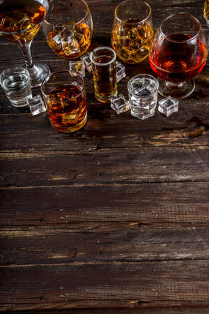 Assortment various hard and strong alcoholic drinks in different glasses: vodka, cognac, tequila, brandy and whiskey, grappa, liqueur, vermouth, tincture, rum, etc. Wooden background copy space Stock Photo