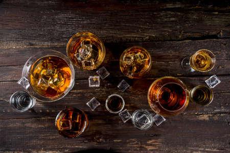 Asortyment różnych twardych i mocnych napojów alkoholowych w różnych szklankach: wódka, koniak, tequila, brandy i whisky, grappa, likier, wermut, nalewka, rum itp. Drewniane miejsce na kopię tła