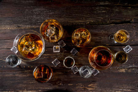 Assortment various hard and strong alcoholic drinks in different glasses: vodka, cognac, tequila, brandy and whiskey, grappa, liqueur, vermouth, tincture, rum, etc. Wooden background copy space Stockfoto