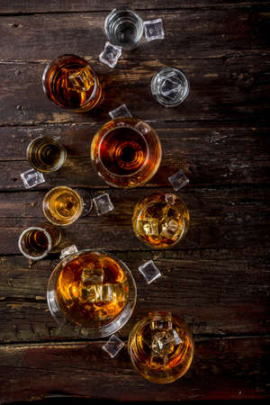Assortment various hard and strong alcoholic drinks in different glasses: vodka, cognac, tequila, brandy and whiskey, grappa, liqueur, vermouth, tincture, rum, etc. Wooden background copy space Foto de archivo