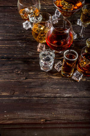 Assortment various hard and strong alcoholic drinks in different glasses: vodka, cognac, tequila, brandy and whiskey, grappa, liqueur, vermouth, tincture, rum, etc. Wooden background copy space Archivio Fotografico