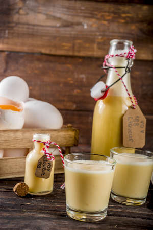 Traditional Italian Vov eggs liquor. German Egg Liqueur Eierlikor. In different bottle and shot glasses, Wooden background copy space