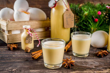 Traditional Italian Vov eggs liquor. German Egg Liqueur Eierlikor. In different bottle and shot glasses, Wooden background copy space with christmas tree decorations