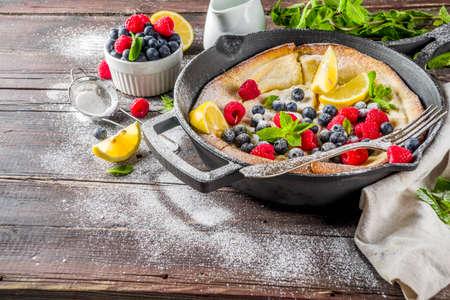 Sweet breakfast vegan dutch baby baked pancake with fruit and berries, wooden background copy space 版權商用圖片