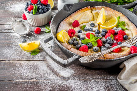 Sweet breakfast vegan dutch baby baked pancake with fruit and berries, wooden background copy space Reklamní fotografie - 124514976