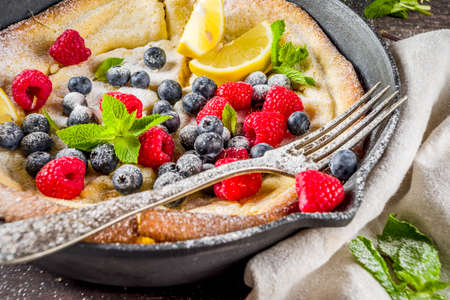 Sweet breakfast vegan dutch baby baked pancake with fruit and berries, wooden background copy space Reklamní fotografie - 124514977
