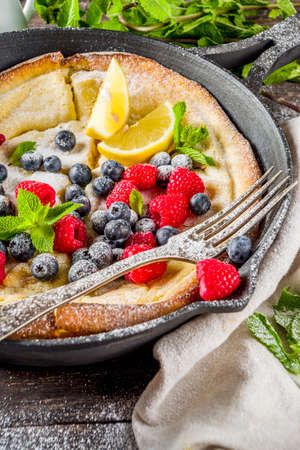 Sweet breakfast vegan dutch baby baked pancake with fruit and berries, wooden background copy space Reklamní fotografie - 124514978
