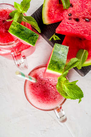 Cold summer drink. Homemade watermelon smoothie. White concrete or stone background copy space