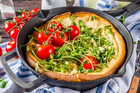 Pancake al forno bambino olandese vegano salato con foglie di insalata e verdure, spazio copia sfondo in legno Archivio Fotografico
