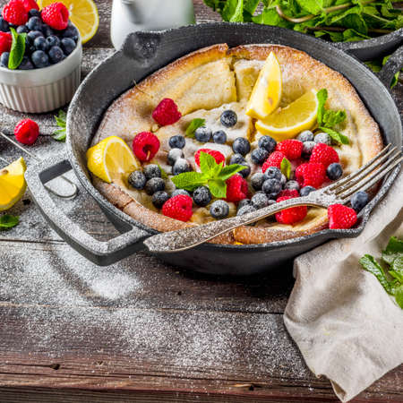 Sweet breakfast vegan dutch baby baked pancake with fruit and berries, wooden background copy space Reklamní fotografie