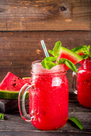 Cold summer drink. Homemade watermelon smoothie. Old wooden background copy space