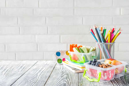 Healthy school lunch box. Kid's lunch box with sandwiches, fruit, vegetables, nuts, water and school supplies, White wooden background Reklamní fotografie - 124634815