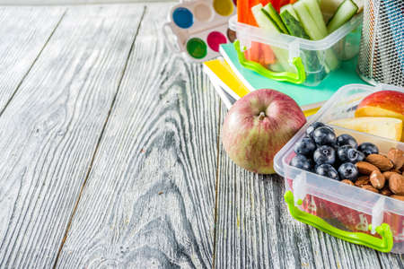 Healthy school lunch box. Kid's lunch box with sandwiches, fruit, vegetables, nuts, water and school supplies, White wooden background Reklamní fotografie - 124634826