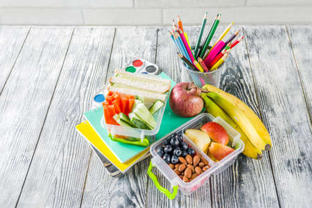 Healthy school lunch box. Kid's lunch box with sandwiches, fruit, vegetables, nuts, water and school supplies, White wooden background Reklamní fotografie - 124634827