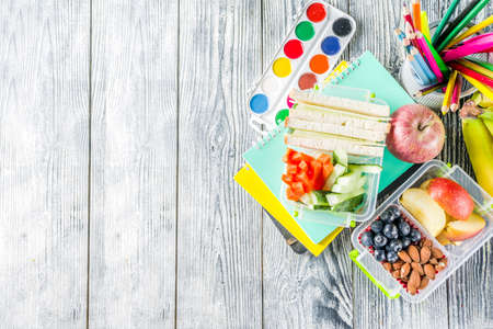 Healthy school lunch box. Kid's lunch box with sandwiches, fruit, vegetables, nuts, water and school supplies, White wooden background Reklamní fotografie - 124634828