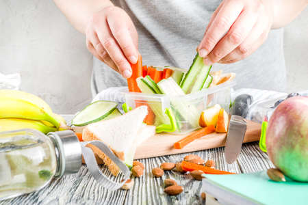 Mother cooking school lunch box set, Preparing healthy snacks - cheese sandwich with cucumber, carrot. nuts, fruits and vegetable in box.