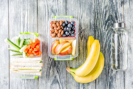 Healthy school lunch box. Kids lunch box with sandwiches, fruit, vegetables, nuts, water and school supplies, White wooden background