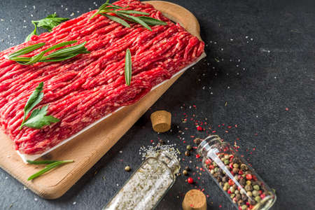 Raw minced beef meat with herbs and spices for cooking, black concrete or stone table Reklamní fotografie