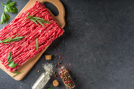 Raw minced beef meat with herbs and spices for cooking, black concrete or stone table Reklamní fotografie - 124927156