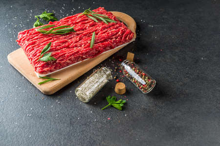 Raw minced beef meat with herbs and spices for cooking, black concrete or stone table Reklamní fotografie - 124927159
