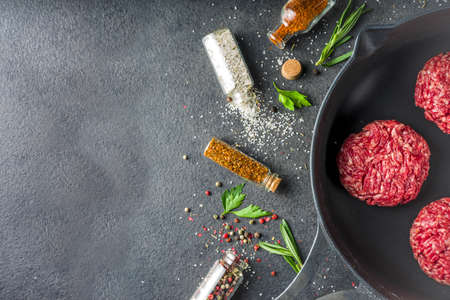 Raw minced meat beef burger cutlets. Cooking meat and burgers background with olive oil. herb, spices, black stone or concrete table, above, copy space Reklamní fotografie - 124927172
