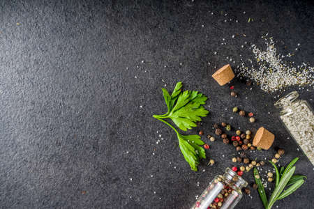 Cooking food background with herbs, olive oil and spices, black stone concrete background above copy space