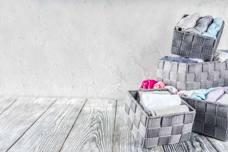 House cleaning concept. Vertical tidying up storage. Marie Kondo tidying method. Neatly folded clothes in the organizer boxes for wardrobe. Wooden background copy space above Stock Photo