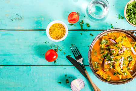 Indian food recipes, Indian Omelet Masala Egg Curry, with fresh vegetables - tomato, hot chili pepper, parsley, light blue wooden background, copy space top view