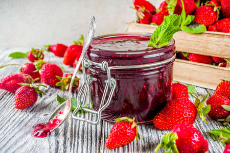 Homemade preservation. Strawberry Jam in small jar, with fresh strawberries, on wooden background copy space Stockfoto - 125096838