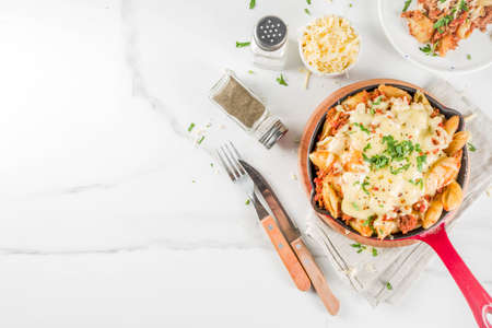 Baked creamy pasta casserole, macaroni and cheese with minced meat, italian ground beef bolognese casserole, dark blue concrete background copy space