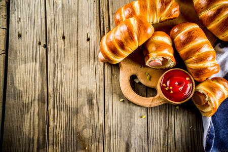 Pretzel wrapped hot dogs with sausages, with ketchup sauce, dark background copy space
