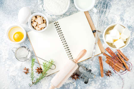 Christmas and winter baking background. Kitchen utensils and ingredients for cooking baking - flour, sugar, eggs, butter, milk, cinnamon sticks, whisk, rolling pin, anise, Blue concrete background copy space top view 写真素材