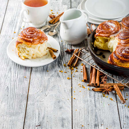 Homemade baking, Cinnamon rolls with sugar frosting. With cinnamon sticks and spices, wooden background copy space 版權商用圖片