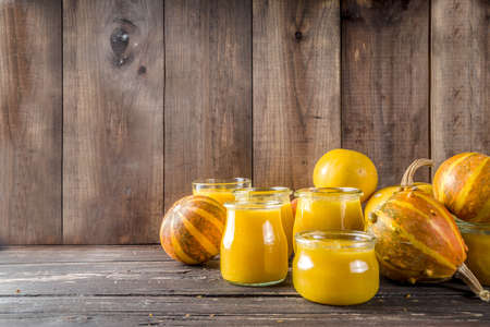 Autumn winter food. Pumpkin puree in different glass jars,with spices, Wooden background copy space