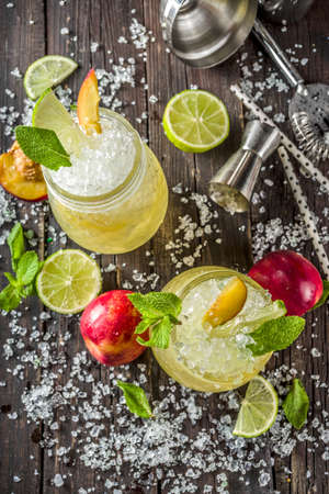 Summer iced peach tea with mint, lime and crushed ice, wooden background copy space Stockfoto
