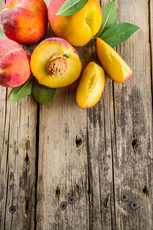 Fresh organic peaches, whole and sliced, with leaves, on rustic wooden background 写真素材