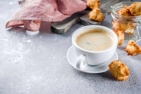 French coconut cookies congolais with coffee mug, grey stone or concrete background copy space Banco de Imagens