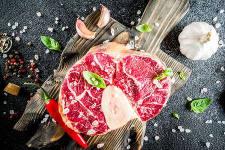 Raw ossobuco meat, beef steak with spices for cooking, black stone concrete