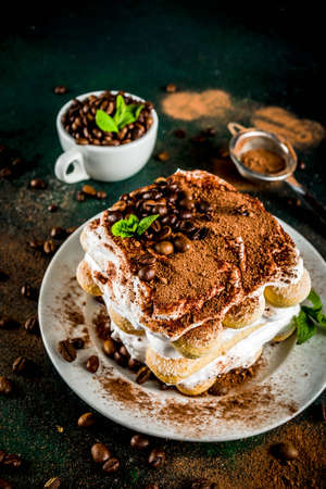 Homemade italian dessert tiramisu on plate, with cocoa and coffee beans, decorated with mint, dark green  copy space