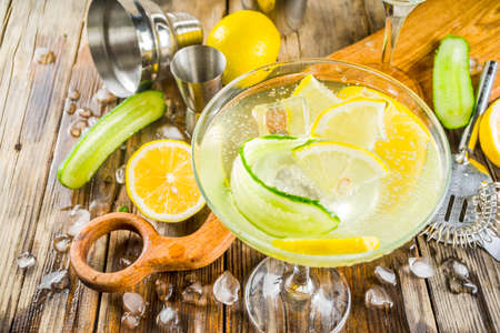 Trendy summer alcohol beverage, Low-Calorie and Low-Carb Tom Collins cocktail, with lemon and cucumber slices, old wooden  copy space