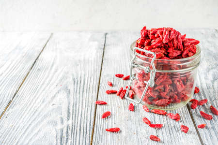 Dried goji berries in little jar, wooden  copy space