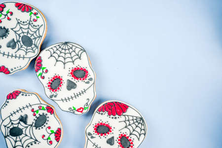 Dia de Los Muertos, Mexican Day of the Dead or Halloween greeting card  with traditional colorful skull shaped cookies with sugar topping candies top view copy space