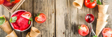Vegetable gelato. Tomato ice cream with fresh tomatoes and basil and leaves, old rustic wooden background. banner format