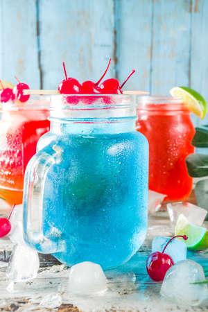 Bebidas frías tropicales de verano. Blue Hawaiian, Tequila sunrise, cócteles de brisa marina sobre fondo de playa de madera azul claro, espacio de copia