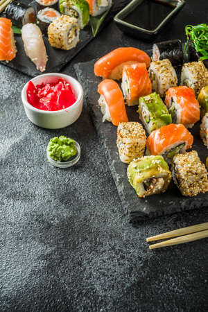 Assorted sushi set on stone or concrete background.  Japanese classic sushi, sushi nigiri. rolls, soy sauce, ginger, chopsticks. Top view. copy space
