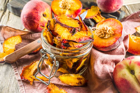 Homemade dried peaches, with fresh whole and sliced peaches, rustic wooden background copy space