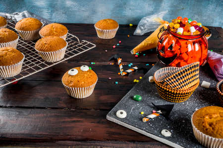 Funny children's treats for Halloween: variations of cupcakes, decorated in the form of different monsters Archivio Fotografico - 126643681